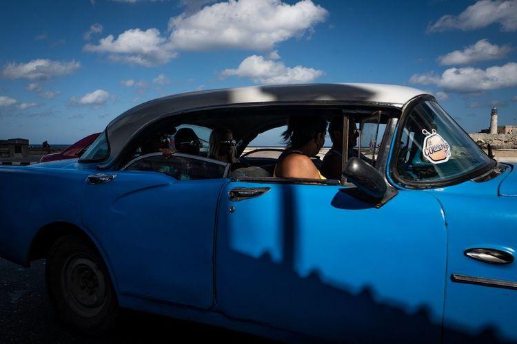 Man driving car against blue sky