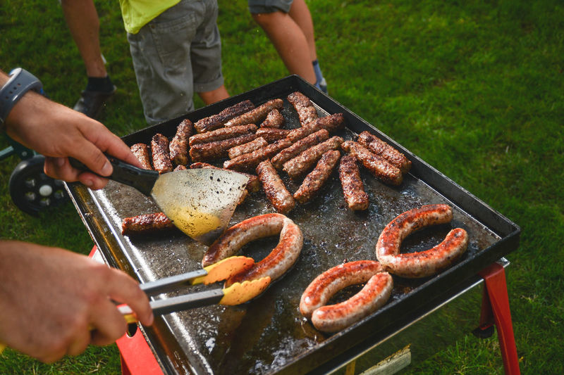 High Angle View Of Men Preparing Sausages On Barbecue Grill In Yard
