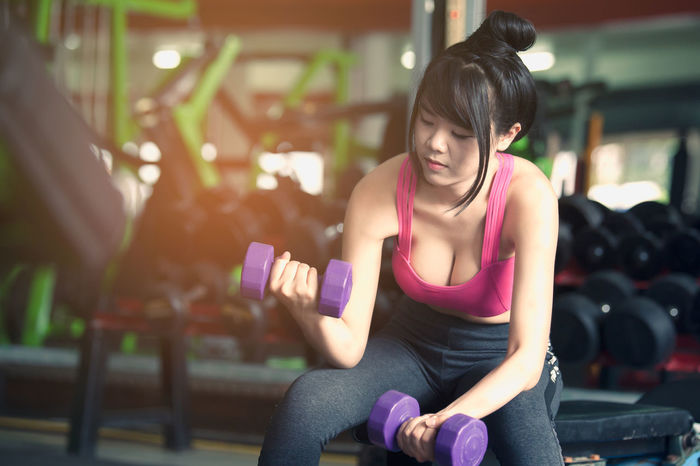 Young woman training with dumbbell in gym Activity Dumbbell Dumbbells Exercise Equipment Exercising Gym Health Club Healthy Lifestyle Lifestyles Muscular Build One Person Sitting Sport Sports Clothing Sports Training Strength Training Wellbeing Women