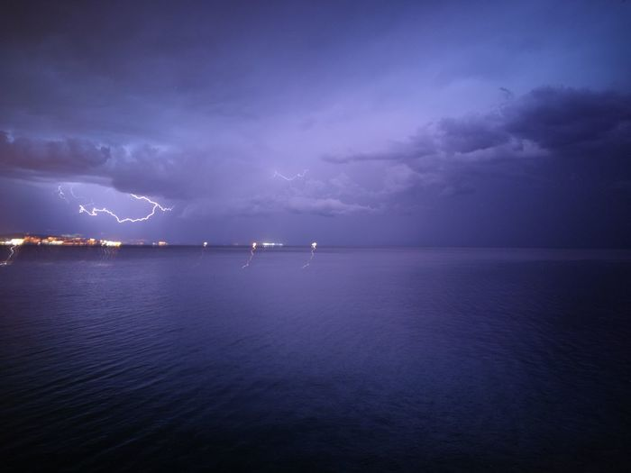 View of lightning strike against calm sea
