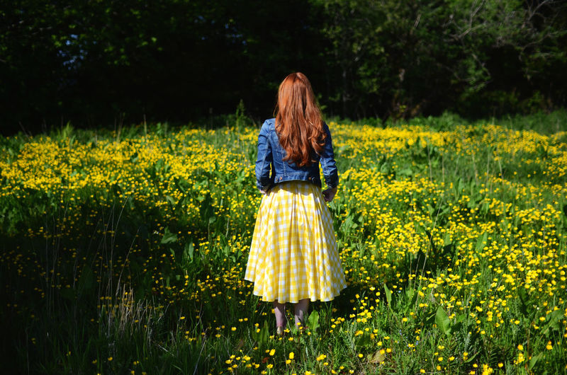 Rear View Of A Red Haired Young Woman On Flower Meadow