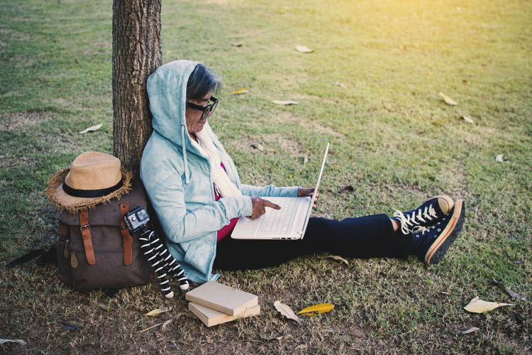 Senior woman using laptop while sitting at park