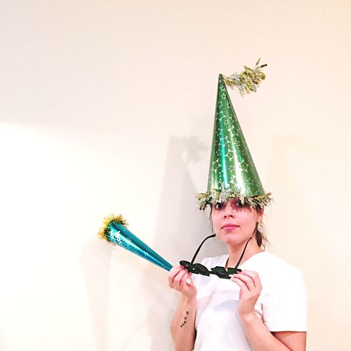 Portrait of young woman wearing party hat over white background