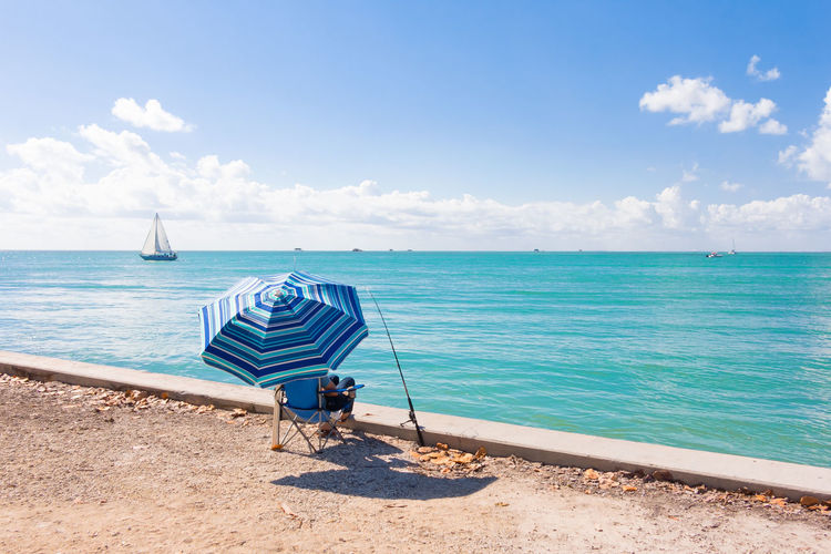 Rear view of man sitting on folding chair by sea