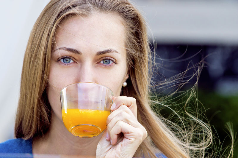 Portrait of woman drinking juice in cup