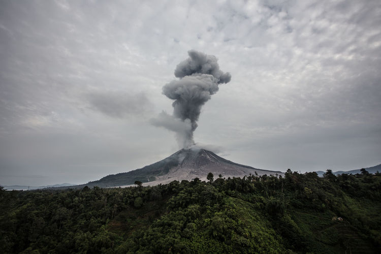 Scenic view of smoke emitting from volcanic crater against sky