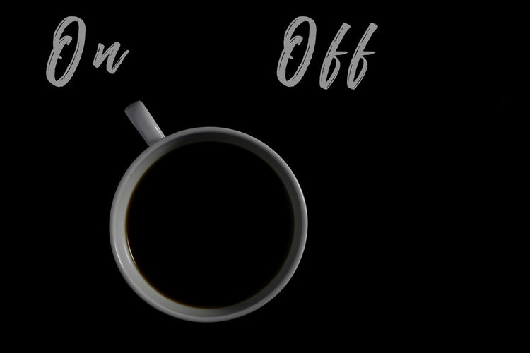 Close-up of coffee cup over black background