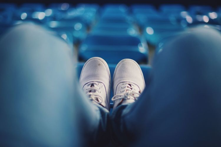 Low section of man sitting on chair at stadium