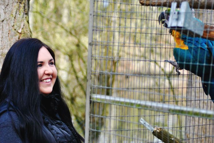 Smiling young woman looking at macaw in cage