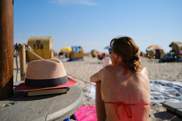 Rear view of carefree woman with backless bikini sitting on beach