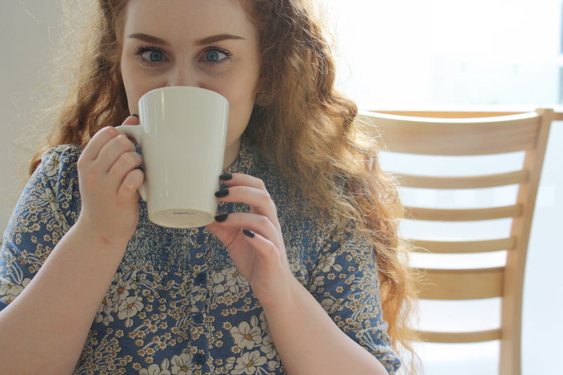 Woman cute eyes while drinking coffee, playful enjoying life Cafe Casual Clothing Close-up Coffee Custard Factory Daisys Drinking A Latte Focus On Foreground Funny Faces Headshot Leisure Activity Lifestyles People Together Portrait Red Hair