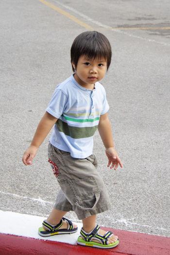 Portrait of cute boy walking on street