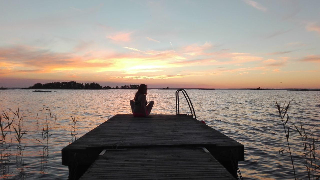 Rear View Of Woman Sitting On Pier Over Sea Against Sky During Sunset