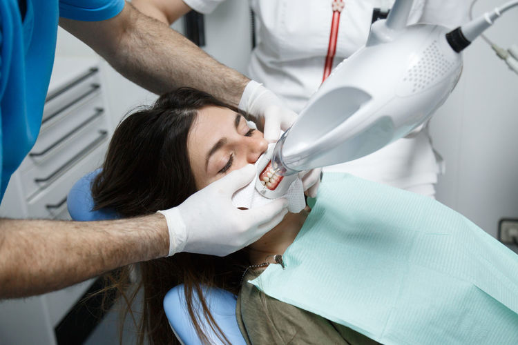 Dentist Treating Patient In Clinic