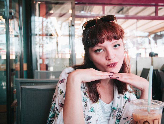 Portrait Of Beautiful Young Woman Puckering At Restaurant
