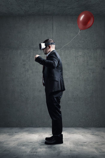 Side view of businessman with balloons wearing virtual reality glasses while standing against gray wall