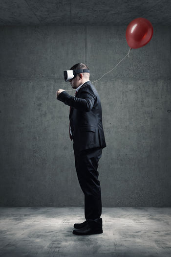 Digital composite image of man with balloon standing against wall