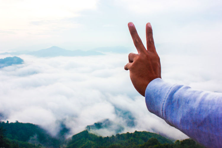 Cropped hand gesturing peace sign against cloudy sky