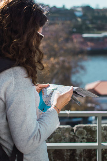 Side view of woman reading map while standing by railing