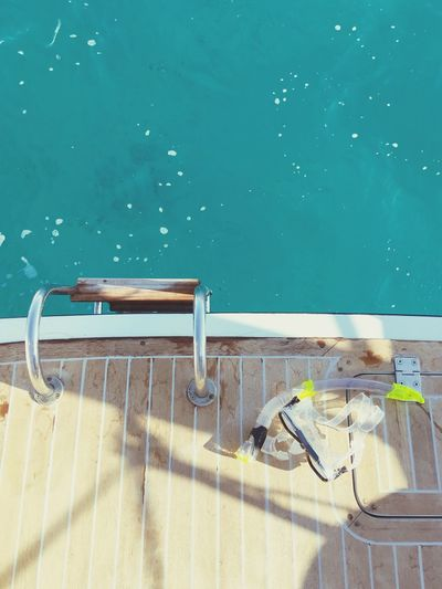 High angle view of snorkel and swimming goggles on boat deck in sea