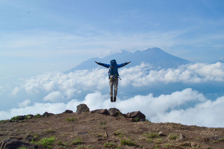 Sky Mountain Arms Outstretched Cloud - Sky Leisure Activity Human Arm One Person Limb Nature Mid-air Day Real People Scenics - Nature Rock Beauty In Nature Environment Lifestyles Tranquility Rear View Tranquil Scene Mountain Range Outdoors