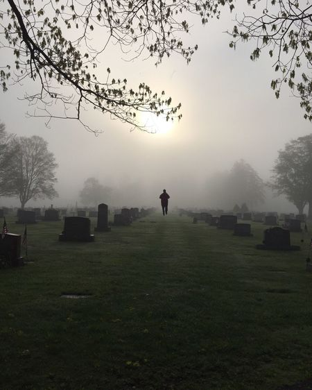 Person Amidst Tombstones At Cemetery During Foggy Weather