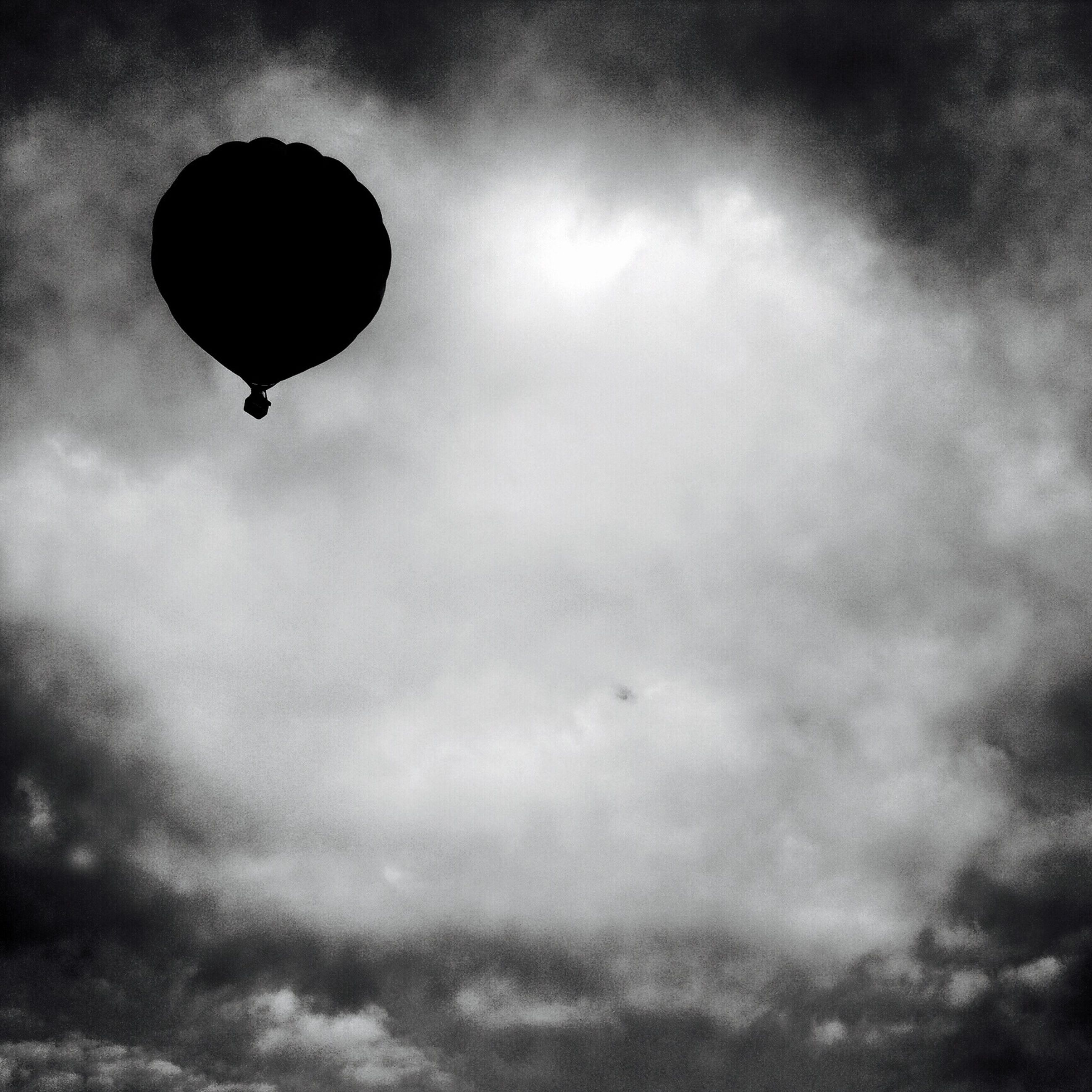 low angle view, sky, flying, mid-air, cloud - sky, cloudy, parachute, hot air balloon, cloud, scenics, adventure, tranquility, nature, beauty in nature, outdoors, dusk, tranquil scene, weather, overcast, no people