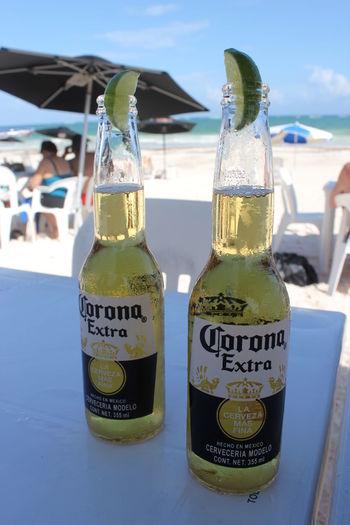 Cold Corona Beach Beers with Lime, Playa Santa Fe, Tulum, Mexico Beach Beers Brand Cerveceria Modelo Cerveza Close-up Cold Corona Corona Extra With Lime  Glass Bottles Hot Lager Lime Made In México Mexican Mexican Culture Mexico Outdoors Sunny Tulum Tulum , Rivera Maya.