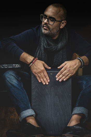 A stylish musician in denim and double monk shoes plays the Cajon, a Peruvian drum used commonly with Spain's Flamenco dance. Asian  Indian Art Artist Beat CAJON Classic Classical Concert Cultural Culture Drum Drummer Eastern Entertainment Ethnic Finger Flamenco Hands India Indoors  Instrument Instrumental Instruments Isolated Live Male Man Melody Music Musical Musical Instruments Musician Percussion Perform Performance Peruvian Play Playing Popular Raga Rhythm Sit Sitting Sound Spanish Tabla Tradition Traditional Wooden