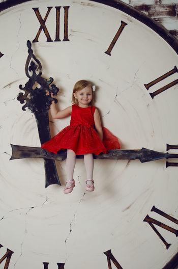 Girl sitting on clock hand