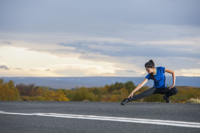 Man running on road against sky