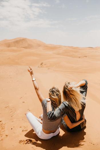 People sitting on sand dune in desert against sky