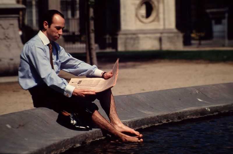 Businessman reading newspaper while sitting by pond in city