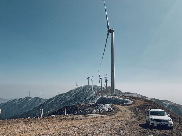 Windmill on mountain against clear blue sky