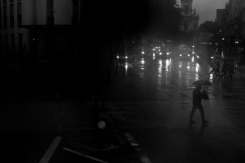Silhouette man walking on illuminated street at night