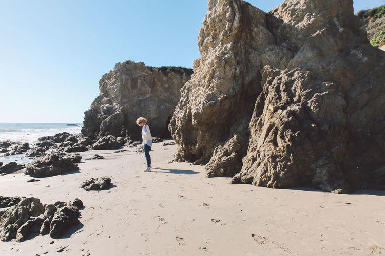 California El Matador Beach Adventure Beach Beauty In Nature Clear Sky Cliff Curly Hair Day Full Length Girl Leisure Activity Lifestyles Nature One Person Outdoors People Real People Rock - Object Rock Formation Scenics Sea Sky Standing Sunlight Water Young Adult