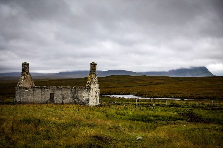Old ruins on grassy field against cloudy sky