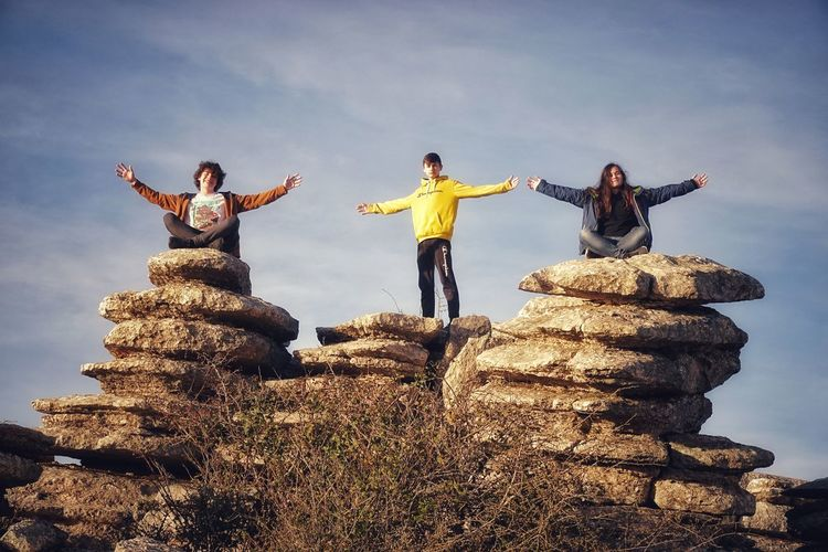 People standing on rock against sky