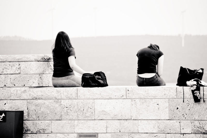 Rear view of women sitting against wall