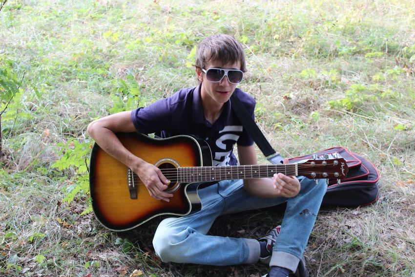 Guitar Music Musical Instrument Plucking An Instrument Guitarist Playing Musician Acoustic Guitar Sunglasses Arts Culture And Entertainment Casual Clothing String Instrument One Person Adults Only Adult Young Adult Outdoors Classical Guitar People Sitting