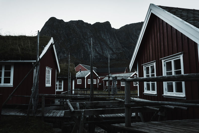 Lofoten Islands Norway Reine Architecture Beauty In Nature Building Exterior Built Structure Cabin Clear Sky Day Desaturated Fishermen's Life Folk Folklore House Mountain Nature No People Outdoors Scenics Sky Tranquility Village Water Wood - Material