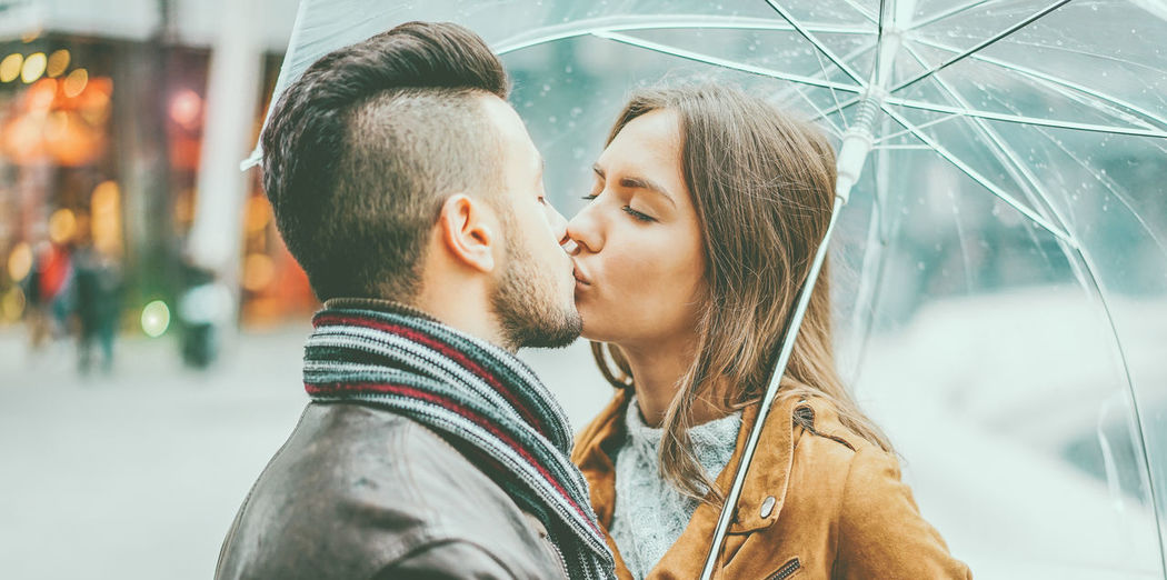 Young couple kissing under umbrella