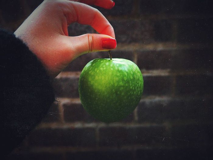 Cropped Hand Of Woman Holding Green Apple Against Wall