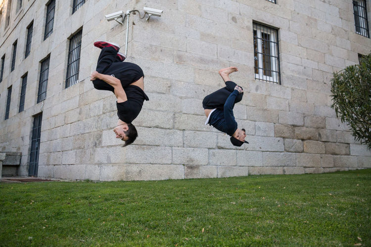 Full length of male friends jumping against building at lawn