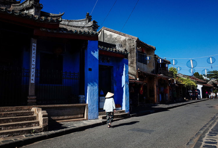 People on street by buildings against blue sky