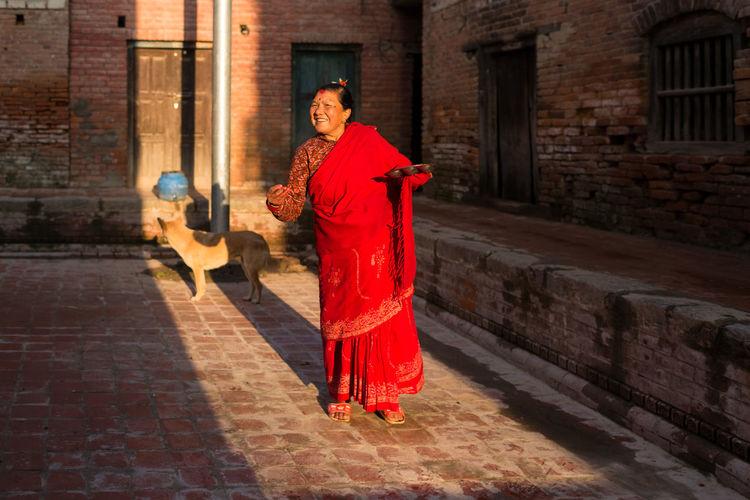 Woman with red umbrella walking on sidewalk