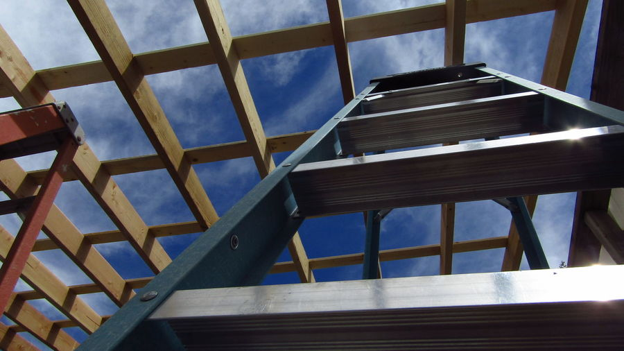Low angle view of ladder and framing against sky