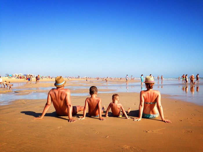 Rear view of family sitting at beach