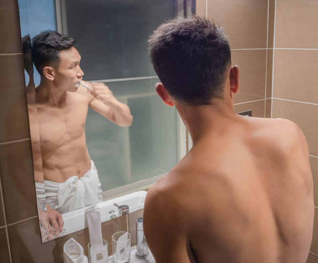 Rear view of shirtless man standing in bathroom