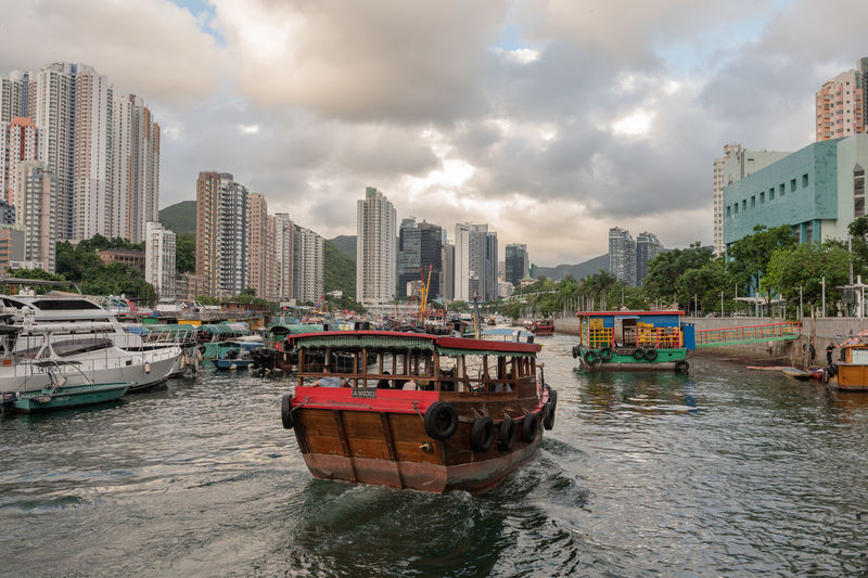 Boats moored on river by buildings in city against sky